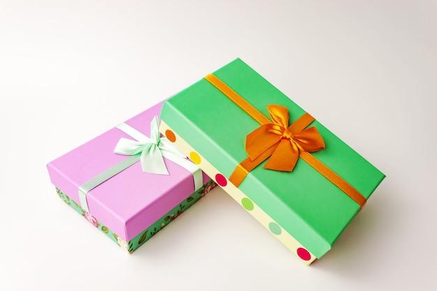 白の弓とギフト紙の段ボール箱をペアにします。ホリデープレゼントのコンセプト。ビューを閉じます。選択的なソフトフォーカス。テキストコピースペース。