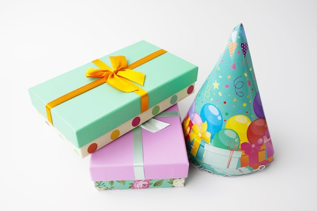 Pair gift paper cardboard boxes with bow and stack of holiday caps on white . birthday party concept. close up view. selective soft focus. text copy space.