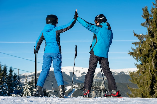 Pair giving high five to each other, smiling, standing with skis on mountain top at a winter resort with ski lifts, mountains and blue sky in background