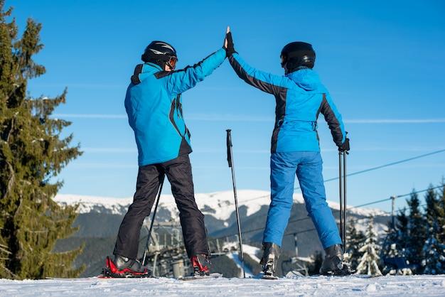 Пара, дающая друг другу высокие пять, с улыбкой смотрит стоя на лыжах на вершине горы