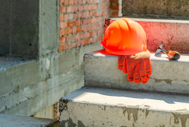 A pair of gloves and a mason's helmet at the construction site of a red brick house.
