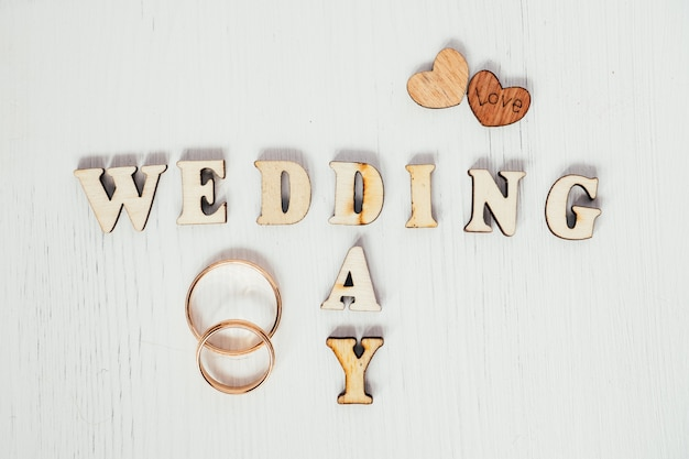 Pair gold rings with two wooden hearts and inscription wedding day on white background.