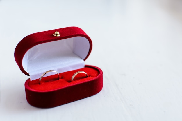 Pair of gold wedding rings lie in a red box