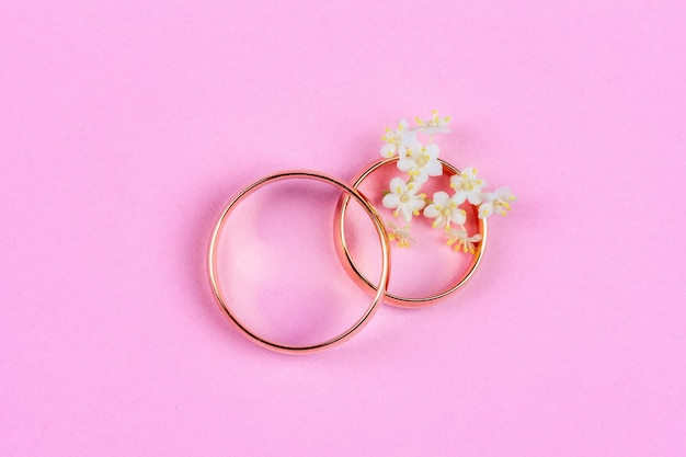 A pair of gold wedding rings and small white flowers in a ring