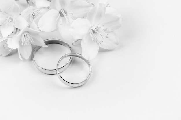Pair of gold wedding rings and white jasmine flowers on white background with copy space