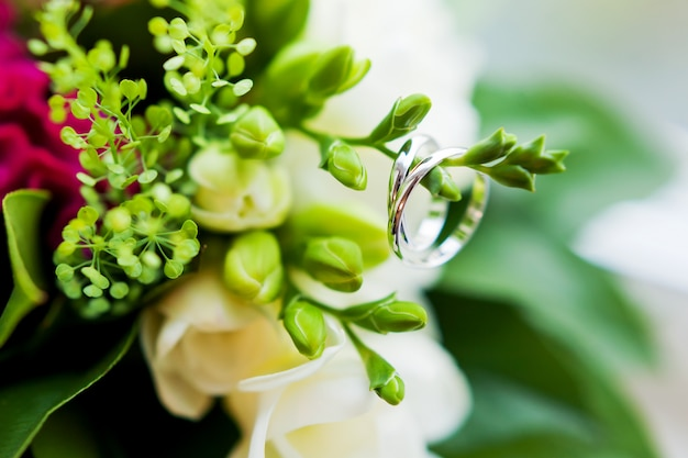 Pair of golden wedding rings inside a bouquet. bride's traditional accessory. floral composition with red celosia flowers.