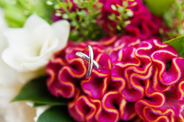 Pair of golden wedding rings inside a bouquetl. bride's traditional symbolic accessory.