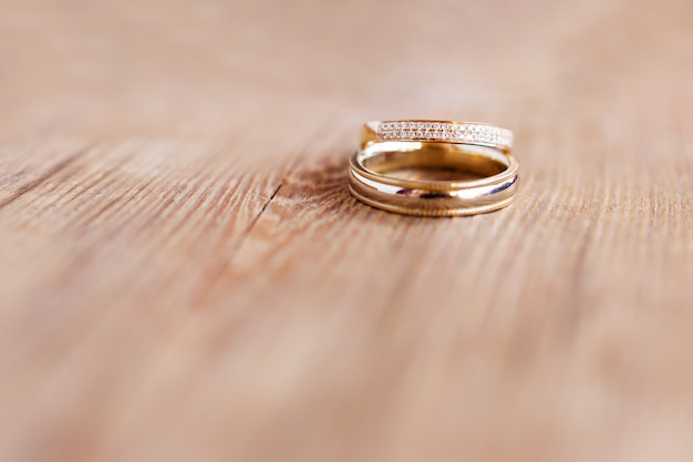 Pair of golden wedding rings with diamonds on shabby wooden surface