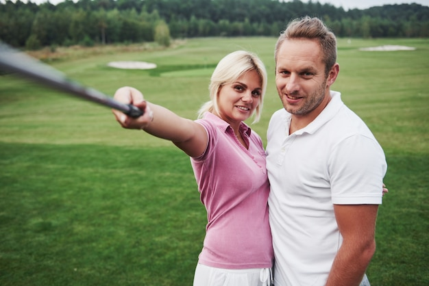 A pair of golfers make a photo on the golf course using a stick like a sephi pole