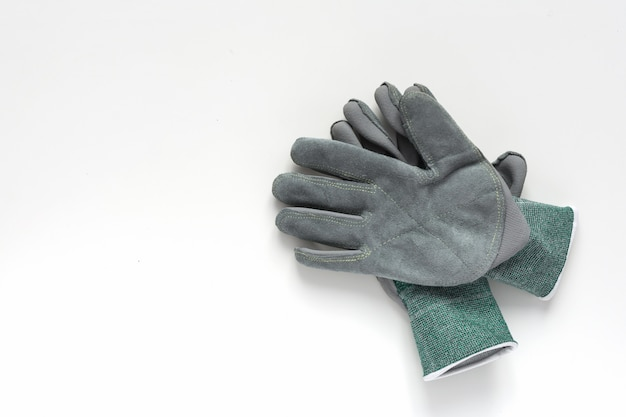 Pair of grey leather work gloves on white background.