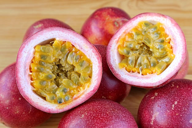 Pair of half cut fresh ripe passion fruit isolated on the whole fruits pile