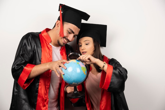 Pair of happy students in gown looking at globe with magnifying glass.