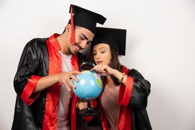 Coppia di studenti felici in abito guardando il globo con lente d'ingrandimento.