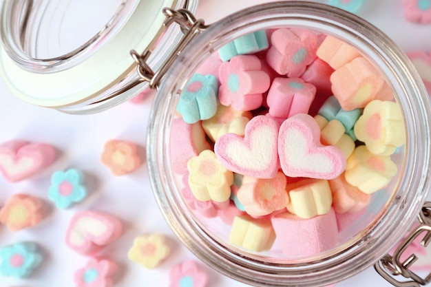 A pair of heart on the pile of pastel flower shaped marshmallow in glass jar with some scattered on the table