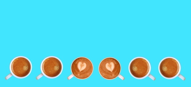 Pair of heart shaped latte art cappuccino coffee with espresso coffees in line on blue background