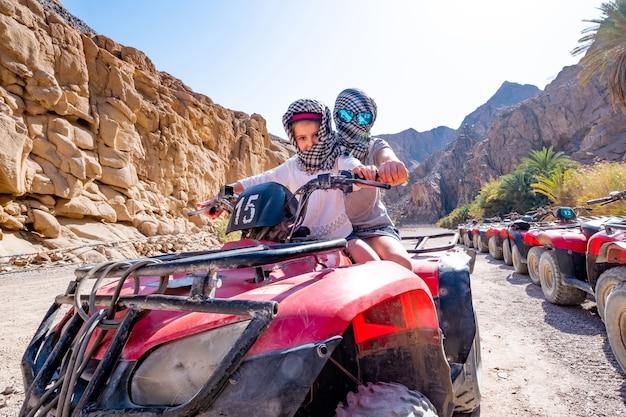 Парный ребенок с тренером катаются на красном квадроцикле в сафари по пустыне