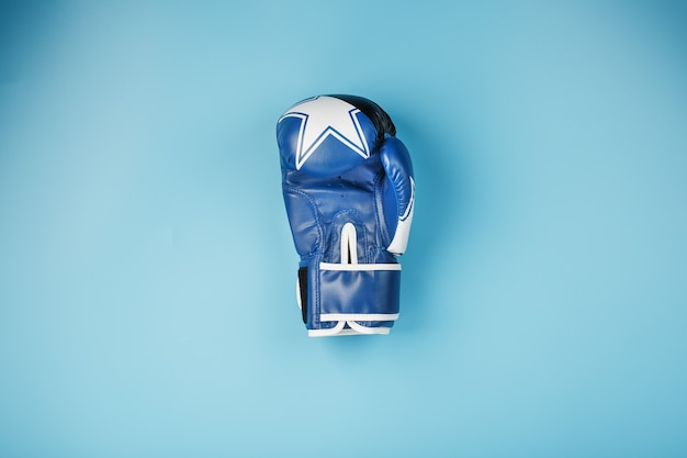 A pair of leather boxing gloves on a blue background, free space.