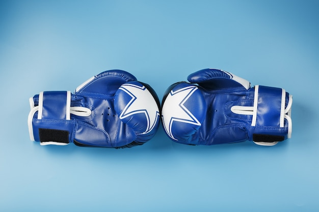A pair of leather boxing gloves on a blue background, free space