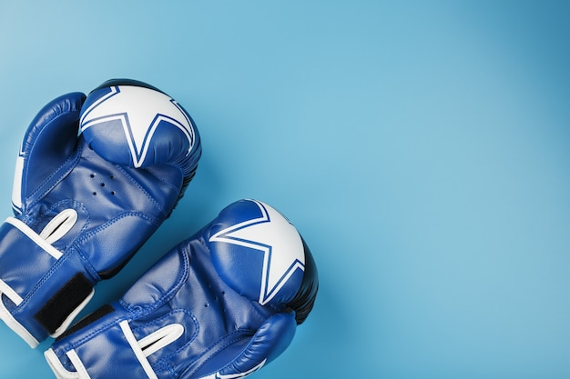 A pair of leather boxing gloves on a blue background