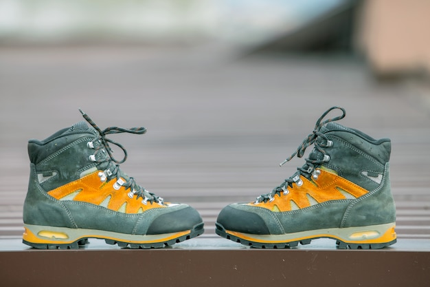 A pair of leather trekking hiking winter boots on blurred background
