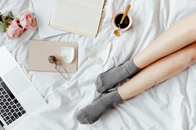 A pair of legs on a white bed sheet