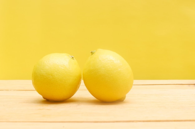 Pair of lemon on the wooden table with yellow background
