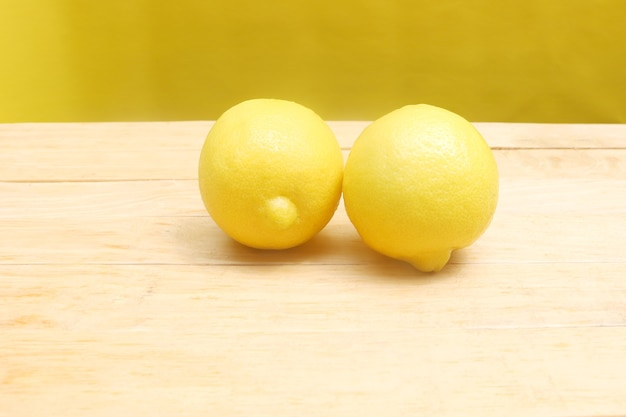Pair of lemon on the wooden table
