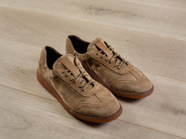 A pair of light suede sneakers on a wooden floor side view