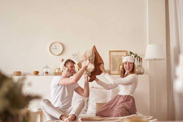 Pair in love laughing and playing on bed. man and woman fight pillows. young happy couple beat the pillows on the bed in a bedroom at home