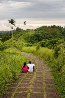 Pair of lovers looks at walking trail between palm trees.