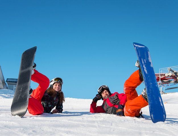 Pair lying with their snowboards on ski slope and looking at the camera with smile