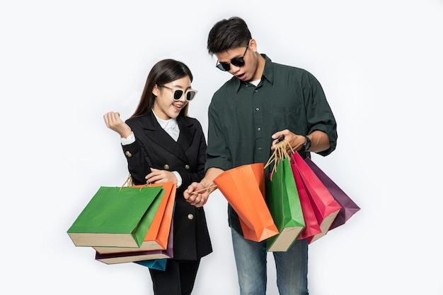 A pair of man and woman wearing glasses and carried lots of paper bags for shopping