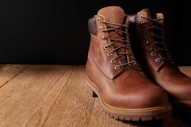 Pair of men leather brown waterproof boots for winter or autumn hiking on wooden table. mens fashion, trendy footwear.