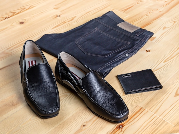 A pair of men's maccassin-style shoes next to jeans and a wallet against a light wooden surface