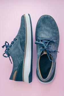 A pair of men's sneakers. blue denim shoes on a pink surface. comfortable textile footwear. view from above. casual fashion style concept.