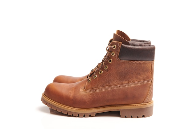 Pair of mens leather brown waterproof boots for winter or autumn hiking isolated. mens fashion, trendy footwear. close up view.