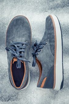 A pair of mens shoes on a gray background.