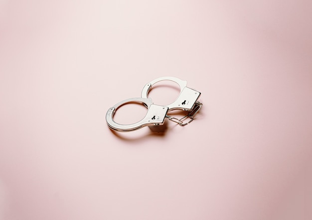 A pair of metallic handcuffs over a flat and bright pastel pink background
