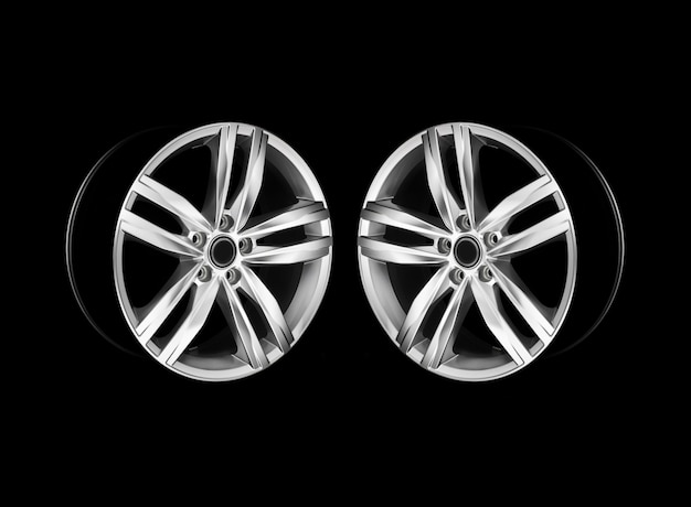 Pair of modern aluminium car wheels in dramatic light. mirrored photo. isolated.