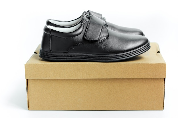 A pair of new black leather boots on the box. the concept of preparing children for school.
