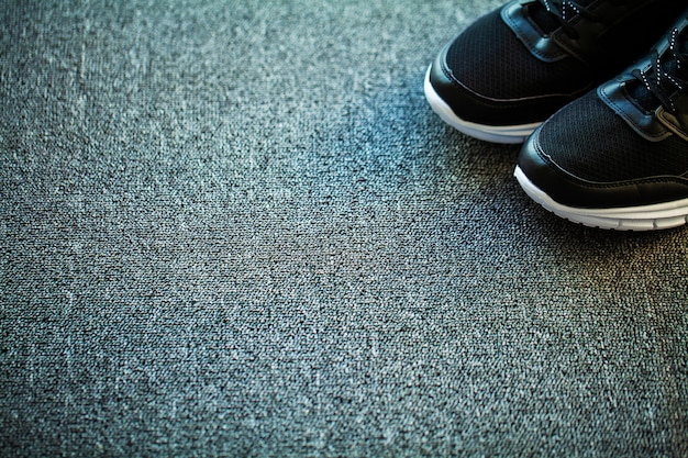 Pair of new stylish black sneakers on floor at home
