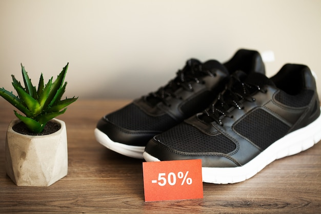 Pair of new stylish black sneakers with discount on gray