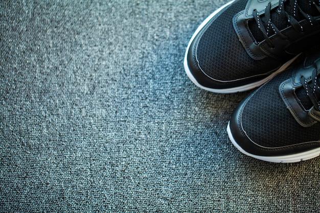 Pair of new stylish sneakers on floor at home.