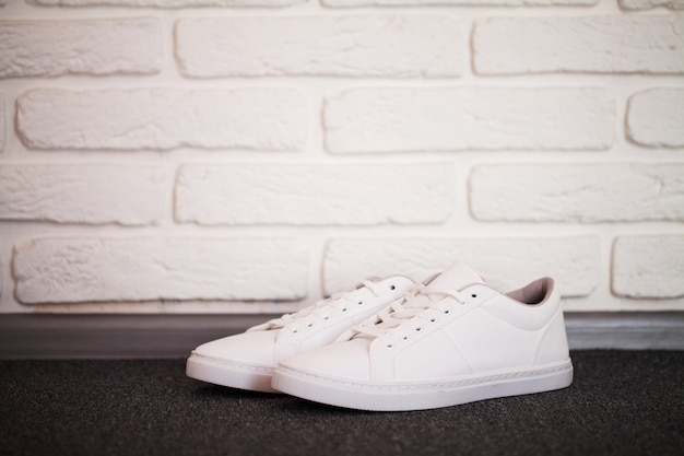 Pair of new stylish white sneakers on floor at home.