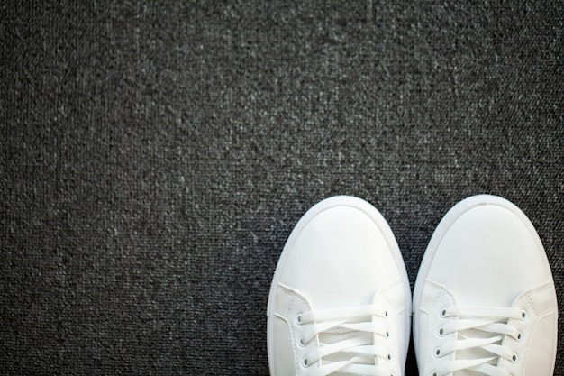 Pair of new stylish white sneakers on floor at home