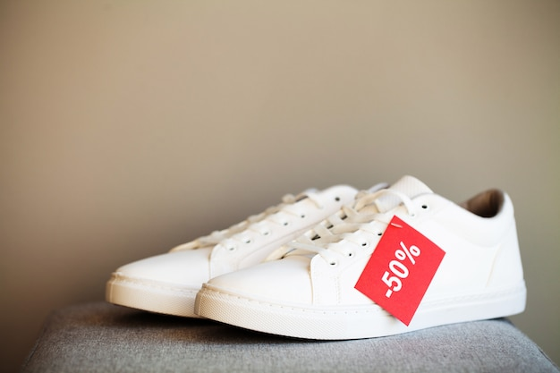 Pair of new stylish white sneakers on floor at store.