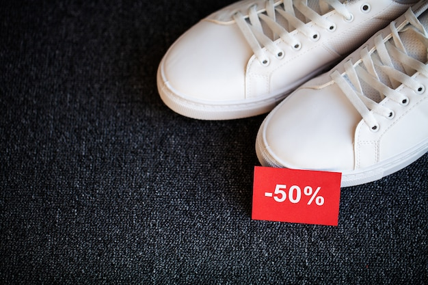 Pair of new stylish white sneakers with discount on gray