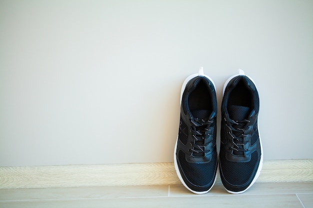 Pair of new stylish white sneakers on wood floor.