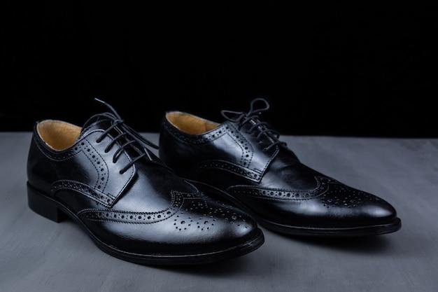 Пара черных туфель на черном фоне. модная мужская обувь. классическая мужская обувь из натуральной кожи. мужские аксессуары. элегантная стильная обувь
