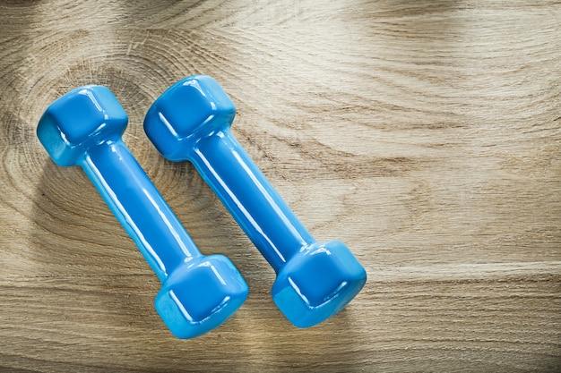 木の板のフィットネスの概念に青いダンベルの重みのペア